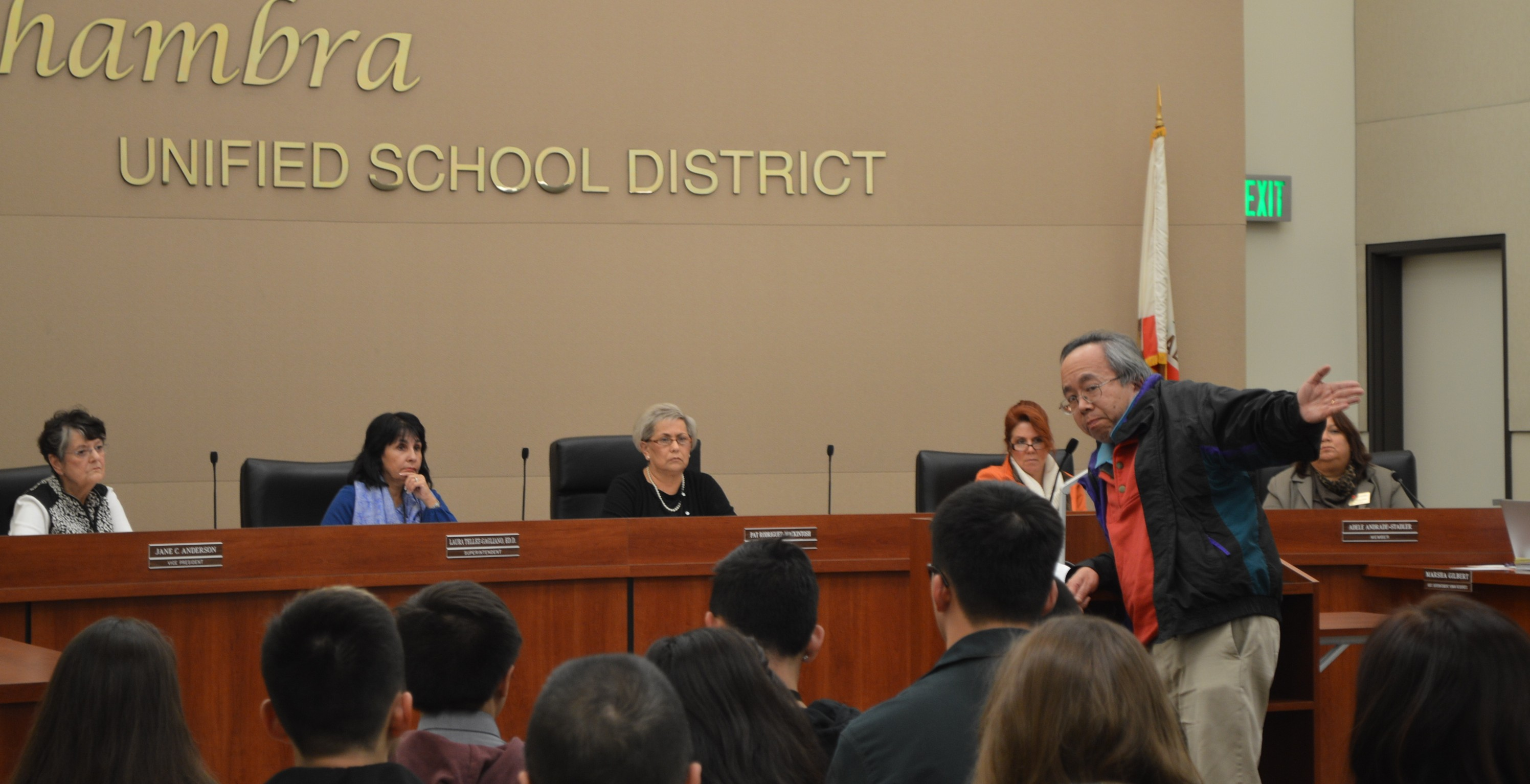 Douglas Chin, Sr. motions to the large amount of faculty, students, and parents in support of Cisneros's return to Mark Keppel during his speech to the AUSD board. THE AZTEC/BRANDON CHUNG