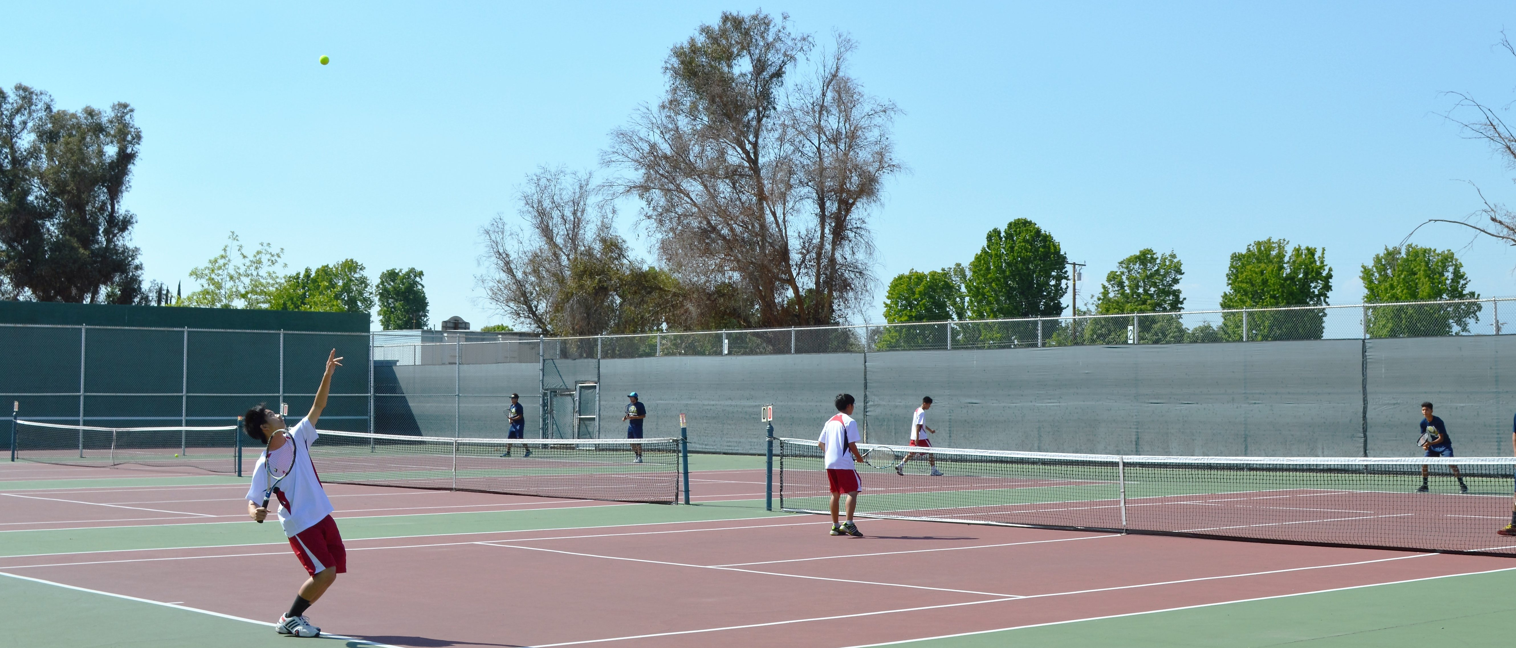 A tennis player serves the ball. THE AZTEC
