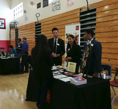 Three bank representatives speaks to another booth's presenter about their profession. THE AZTEC NEWS/CALLISTA LIU
